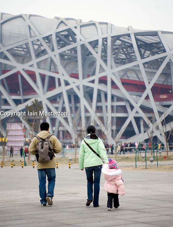 Family with single child walking towards Bird`s Nest Olympic Stadium in Beijing 2009