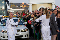 © Licensed to London News Pictures. 19/05/2012. Lands End, UK. 18 year old Tassy Swallow passes on the Olympic flame to Eric Smith at Lands End, Cornwall as part of the 70 day relay across the UK.. Photo credit : Ashley Hugo/LNP