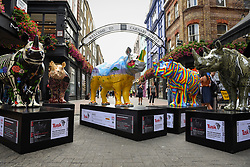 **CAPTION CORRECTION - Rhino statues are 750mm tall, not 750cm tall, as stated in previous captions**<br /> © Licensed to London News Pictures. 20/08/2018. LONDON, UK. Painted rhinos presented at a photocall in Carnaby Street, (L to R) by David Mach, The Chapman Brothers, Ronnie Wood, Patrick Hughes and Adam Dant.  At 750mm tall and weighing 300 kg, each rhino has been specially embellished by an internationally renowned artist.  21 rhinos are in place at a popular location in central London, forming the Tusk Rhino Trail, until World Rhino Day on 22 September to raise awareness of the severe threat of poaching to the species' survival.  They will then be auctioned by Christie's on 9 October to raise funds for the Tusk animal conservation charity.  Photo credit: Stephen Chung/LNP
