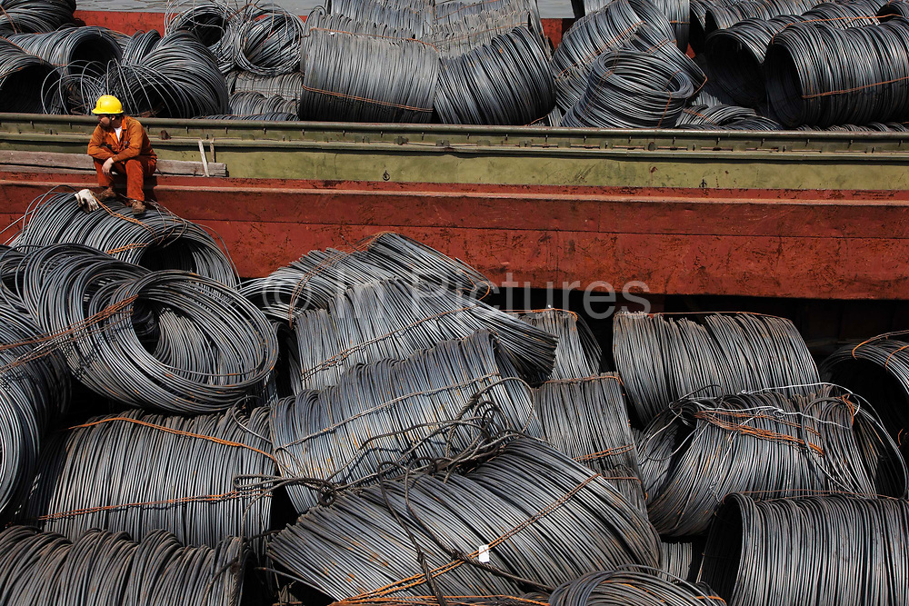 Workers rest on a barge full of steel wires docked at a steel stockyard run by the Shanghai Yirong Trading Company Ltd in Shanghai, China on 10 April 2009. China is world's largest steel producer and consumer, its seemingly insatiable appetite for raw material to fuel its economic growth has been the most important reason behind the recent commodities boom and wealth accumulated by western mining companies.