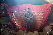 The new husband stands in front of the hangig red cloth behind which his wife is hidden. At the camp of Tash Seri (Mustafa Qol's camp)..Ikhbal will stay there for a few days. She will sleep here, be fed here etc..With Ikhbal, the recently married woman  moving for the first time to her husband's camp..She just exchanged the red veil of the unmarried girl for the white veil signifying that she is now a married woman...Trekking through the high altitude plateau of the Little Pamir mountains, where the Afghan Kyrgyz community live all year, on the borders of China, Tajikistan and Pakistan.