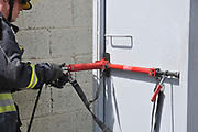 Fire fighter uses hydraulic tools to breach a locked door