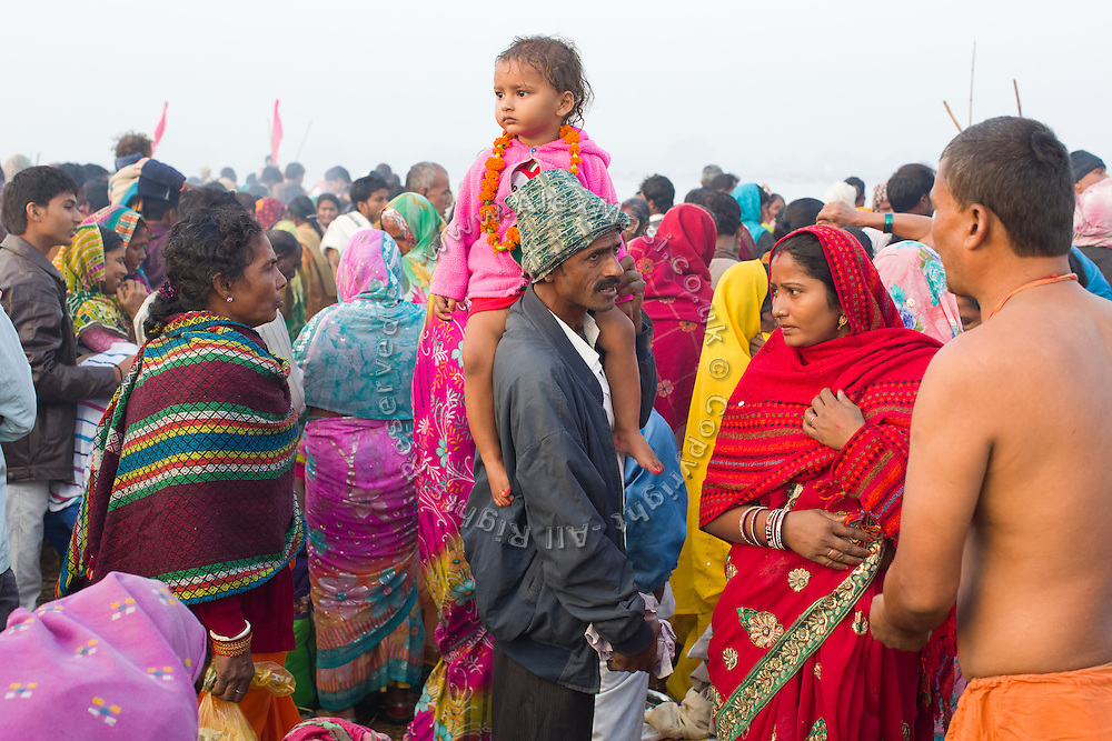A father with his daughter on his shoulder are walking through a crowd of Hindu devotees near a bathing ghat (riverside) on the holy Ganges River during the yearly Sonepur Mela, Asia's largest cattle market, in Bihar, India.