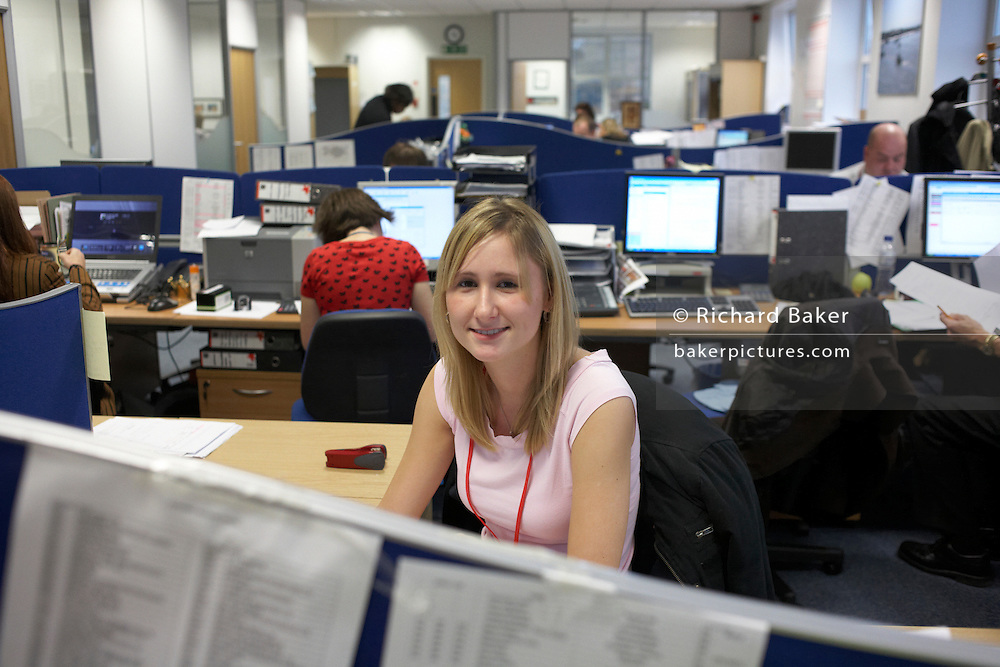 A young girl pauses her duties, sitting at her desk with work colleagues at work in the background of an open plan office