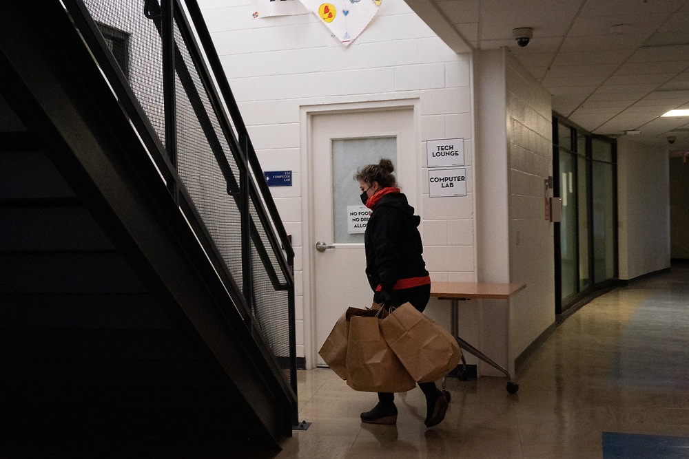 Marina Ivanova, 45 and Assistant General Manager of Medium Rare carries meals into Raymond Community Center in Washington, DC on Wednesday, November 25th, 2020. Medium Rare chef and owner Mark Bucher's organization Feed the Fridges provides free daily restaurant-made meals in public refrigerators across Washington, DC.