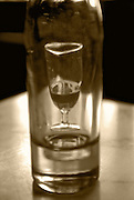 wine glass,half filled,with empty wine bottle on table,sepia,vertcle