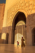 Side view of woman and boy walking by Hassan II Mosque in Casablanca, Morocco