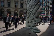 City workers pass-by the giant artwork of a bronze wing<br /> during a spring lunchtime in London's financial district. The ten-metre-tall bronze sculpture is by President of the Royal Academy of Arts, Christopher Le Brun, commissioned by Hammerson in 2009. It is called 'The City Wing' and has been cast by Morris Singer Art Founders, reputedly the oldest fine art foundry in the world.