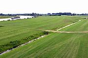 Nederland, the Netherlands, Brummen, 10-5-2018 Het landschap tussen Voorst en Cortenoever, vlakbij Zutphen, is een gebied dat door de IJssel is gevormd. Met uitgestrekte uiterwaarden, stroomruggen en een aantal scherpe rivierbochten. Om het gebied langs de IJssel te beschermen tegen hoogwater zijn op twee plekken dijken landinwaarts verlegd. Zo is er meer ruimte voor de rivier wanneer het nodig is. Bij het verhogen van de waterveiligheid is op een slimme manier gebruik gemaakt van bestaande dijken in het gebied. Die zijn op strategische locaties – in het noorden en zuiden – verlaagd. Bovendien hebben de drempels verschillende hoogten. Daardoor stromen de uiterwaarden bij hoogwater gecontroleerd mee met de rivier en blijft de stroomsnelheid beperkt. Zo treedt er minder schade op. Als de waterstand in de IJssel weer zakt, zakt ook de waterstand in de overstroombare gebieden. Nieuw aangelegde gemalen pompen dan het laatste water uit het gebied, waardoor het snel weer droog is. Foto: Flip Franssen