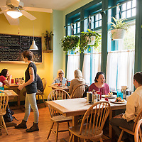"""A waitress takes orders while people dine. The Early Girl Eatery is a self-described """"farm to table southern comfort food experience."""" It is located at 8 Wall Street in Downtown Asheville, North Carolina."""