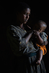 Fifteen-year-old Destaye stands at the door with her son near Bahir Dar, Ethiopia on Aug. 12, 2012. Destaye and her husband Addisu, 27, divide their time between working in the fields and taking care of their 6-month-old baby. Like many other young couples, they tend to the domestic, economic and personal demands of being young parents. At the time of their marriage, when Destaye was age 11, she was still in school and her husband expressed interest in letting her continue her education. Since the birth of their son, however, she has had to confine her life exclusively to being a wife and mother.