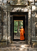 A Buddhist monk standing in the doorway to an ancient temple of Angkor, Siem Reap Province, Cambodia