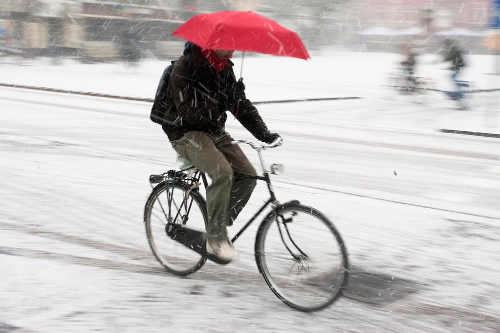 Een man fietst met een paraplu door de sneeuw in Utrecht
