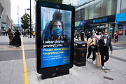 HM Government, Public Health England, NHS advertising boards advise people to take precaution of wearing a face mask, which became compulsory in shops on the 24th July, go out shopping in the city centre on 5th August 2020 in Birmingham, United Kingdom. Coronavirus or Covid-19 is a respiratory illness that has not previously been seen in humans. While much or Europe has been placed into lockdown, the UK government has put in place more stringent rules as part of their long term strategy, and in particular social distancing.
