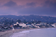 Overlooking waterfront town and sandy coast shore in evening light at Laguna Beach, California