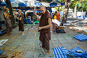 23 MAY 2014 - BANGKOK, THAILAND: A Buddhist monk supporting the anti-government protests takes down his tent in the monks' camping space at the anti-government protest site. The Thai military seized power in a coup Thursday evening. They suspended the constitution and ended civilian rule. This is the 2nd coup in Thailand since 2006 and at least the 12th since 1932.    PHOTO BY JACK KURTZ
