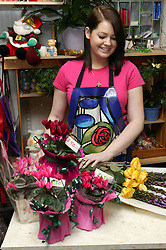 Florist wrapping up flowers for sale in flower shop,