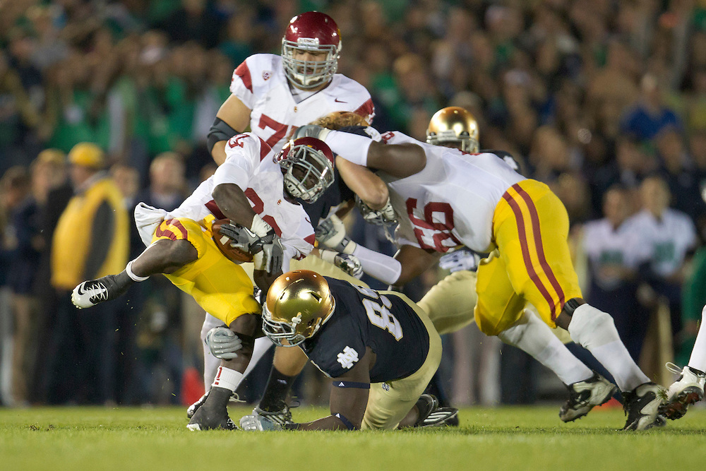 Notre Dame defensive end Kapron Lewis-Moore (#89) tackles USC running back Curtis McNeal (#22) during first quarter of NCAA football game between Notre Dame and USC.  The USC Trojans defeated the Notre Dame Fighting Irish 31-17 in game at Notre Dame Stadium in South Bend, Indiana.