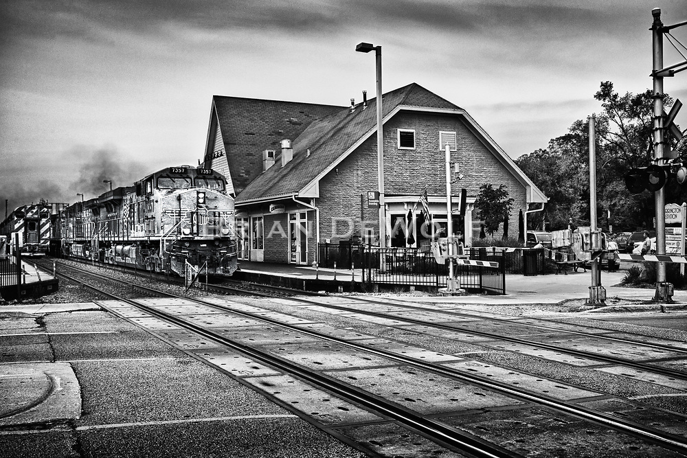 A Chicago-bound freight passes a stopped commuter train at Herrington Station in Geneva, Illinois.