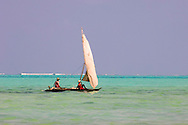 Two men on a traditional wooden dhow with sail.  Zanzibar, Tanzania