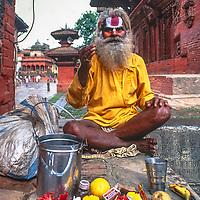 A hindu ascetic sits outside a temple in Kathmandu, Nepal, 1996.
