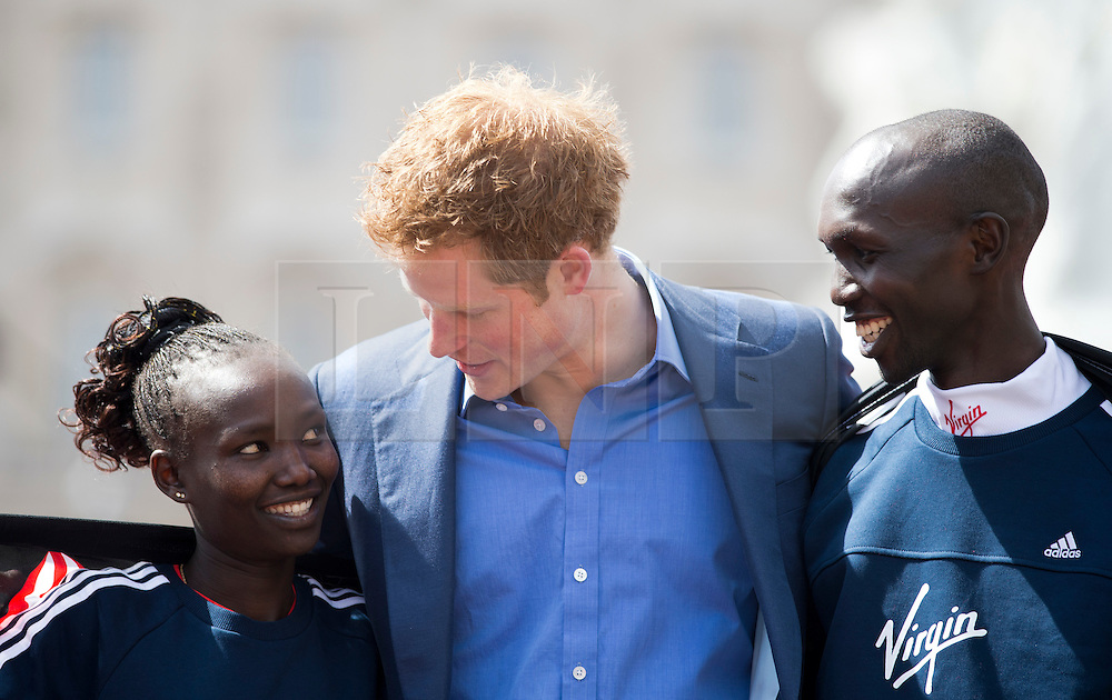 © London News Pictures. 22/04/2012. London, UK. HRH Prince Harry  with Mary Keitany of Kenya (left) and Wilson Kipsang of Kenya (right) on the winners podium after presenting Keitany and Kipsang with their trophies for winning the elite races at the 2012 Virgin London Marathon on April 22, 2012. Photo credit : Ben Cawthra /LNP