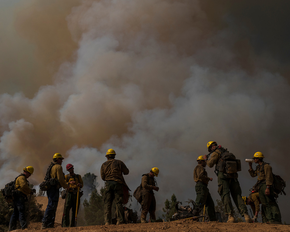 Firefighters from Vandenberg Air Force Base take a rest while fighting the Dolan Fire near Big Sur, Calif. on Sept. 16, 2020.