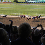 Spectators in the stands watch the field head down the final straight during the 146th Running of the Belmont Stakes,  won by  from Commissioner and Medal Count with California Chrome finishing forth. Belmont  Park, Elmont. New York.  USA. 7th June 2014. Photo Tim Clayton