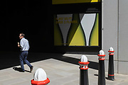 A city worker holding an ice cream walks into dark shadows on Fenchurch Street, on 29th July 2020, in London, England.