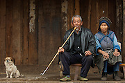 Naxi man smoking long-stemmed bamboo pipe<br /> Lijiang  Yunnan Province<br /> CHINA<br /> The city was founded in the wake  of Kubilai Khan's campaign against the Kingdom of Dali. The Naxi had helped the Mongol army cross the Jinshajiang and when the Khan subsequently arrived in Lijiang he set up his camp around what is now the Old Stone Bridge. The Naxi at the time were living in the northern part of the plain. When their chieftan, the head of the Mu Family, was invested with the Khan's authority to rule the area in the service of the Mongols, the Naxi moved their political center to the vacated camp and built the city of Dayan.<br /> Naxi ethnic minority people migrated out of the highlands of eastern Tibet into Lijiang County beginning of the 1st century A.D.<br /> The woman's costume is dominated by the seven-starred cape.