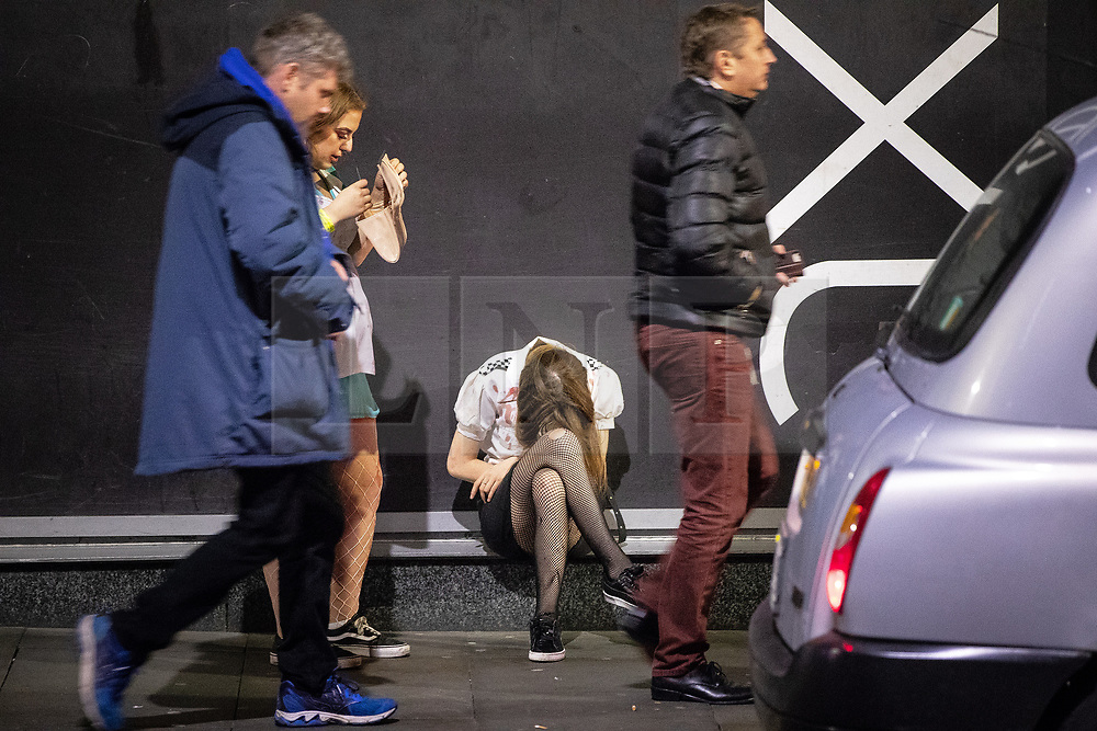 © Licensed to London News Pictures . 28/10/2018. Manchester, UK. A woman slouches forward with her head resting on her knee outside the Printworks , in Manchester City Centre . Revellers on a night out , many in fancy dress , on the weekend before Halloween . Photo credit: Joel Goodman/LNP