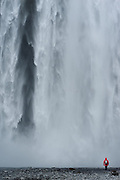 Lone traveller at the base of the Skógafoss waterfall, Iceland