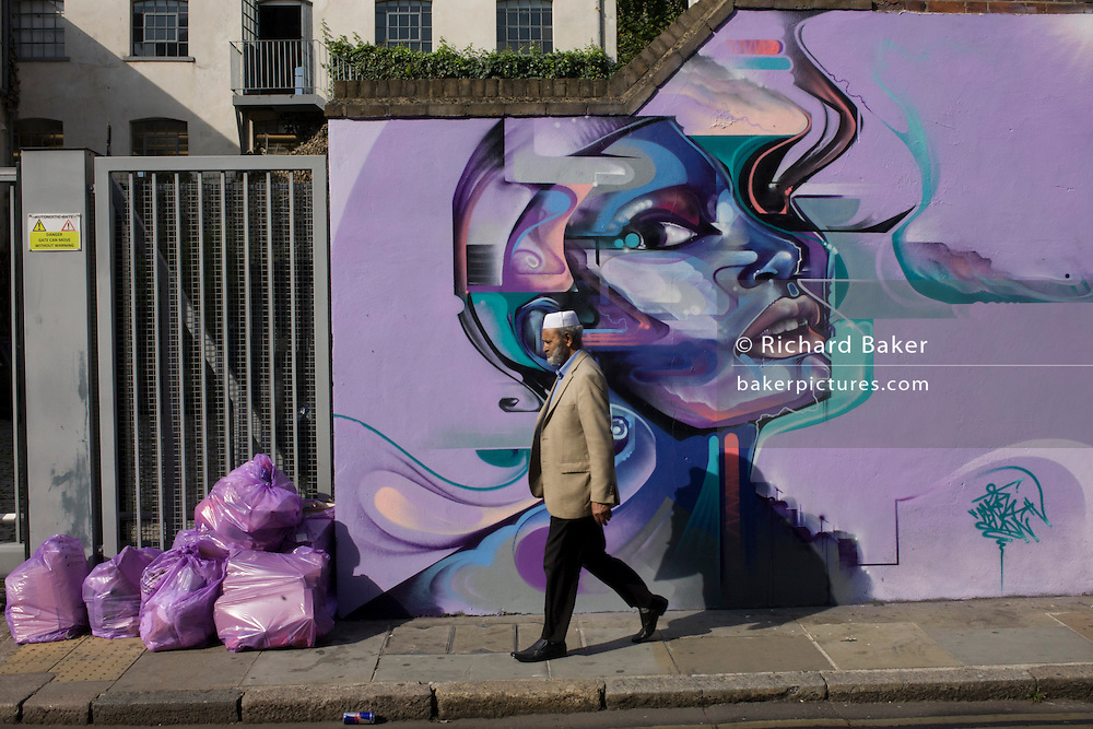 A Muslim man walks past street art on a wall near Brick Lane, London.