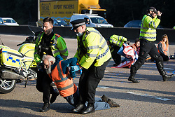 Ockham, UK. 21st September, 2021. Surrey Police officers haul an Insulate Britain climate activist from the clockwise carriageway of the M25 between Junctions 9 and 10 where they had been protesting as part of a campaign intended to push the UK government to make significant legislative change to start lowering emissions. Both carriageways were briefly blocked before being cleared by Surrey Police. The activists are demanding that the government immediately promises both to fully fund and ensure the insulation of all social housing in Britain by 2025 and to produce within four months a legally binding national plan to fully fund and ensure the full low-energy and low-carbon whole-house retrofit, with no externalised costs, of all homes in Britain by 2030.