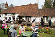 Customers in the garden at The Withies Inn traditional country pub in Compton, Surrey, UK. This public house with tiled roof dates from the 16th century.
