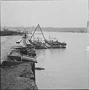 ackroyd-P054-16. Wind damage on Swan Island, February 8, 1965 Barge pumping stations 15A and 16A tied up to Swan Island in the channel. Buildings on the left are on Swan Island, building on right edge is feed mill in Mocks Bottom