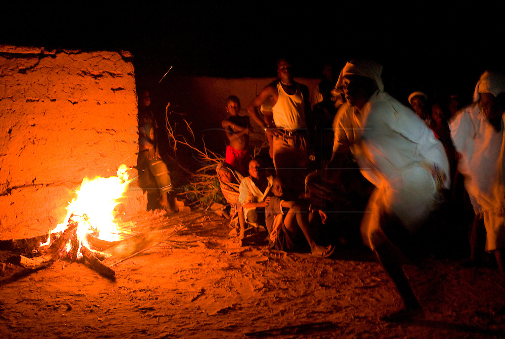 A group of young people performs for tourists a traditional dance by the fire. Dogon youth are trying to take advantage of the benefits brought by tourism to their ethnic group.  The Dogon Country is the most visited part of Mali with tourists visiting its tipical  villages that can be located on the cliff, on the sandy plain or in the rocky plateau