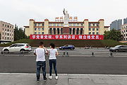 Visitors take pictures in front of a statue of former Chinese leader Mao Zedong in front of the Sichuan Science and Technology Museum in Chengdu, China, on Monday, Sept. 19, 2016. China faces unprecedented challenges as it restructures its economy away from old-line heavy manufacturing and toward consumption and services.