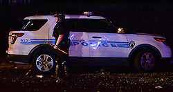A CMPD officer stands near a vandalized vehicle on Old Concord Rd. on Tuesday night, Sept. 20, 2016 in Charlotte, N.C. The protest began on Old Concord Road at Bonnie Lane, where a Charlotte-Mecklenburg police officer fatally shot a man in the parking lot of The Village at College Downs apartment complex Tuesday afternoon. The man who died was identified late Tuesday as Keith Scott, 43, and the officer who fired the fatal shot was CMPD Officer Brentley Vinson. Photo by Jeff Siner/Charlotte Observer/TNS/ABACAPRESS.COM