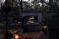 An elderly woman lights a candle on a grave in Rakowicki cemetery in Krakow, Poland 2019.