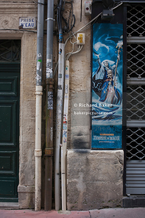 A poster for fantasy game Warhammer alongside power cables and drainpipes in a side street of Montpellier, south of France.