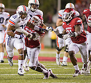 Auburn running back Tre Mason (21) gets past Arkansas safety Eric Bennett (14) as safety Jerico Nelson (31) pursues during an NCAA college football game on Saturday, Oct. 8, 2011, in Fayetteville, Ark. (AP Photo/Beth Hall)