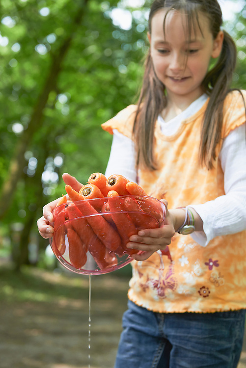 Girl holding plate of washed carrots at picnic, Munich, Bavaria, Germany
