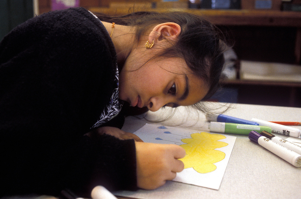 Young Asian child drawing and colouring at a Primary school,