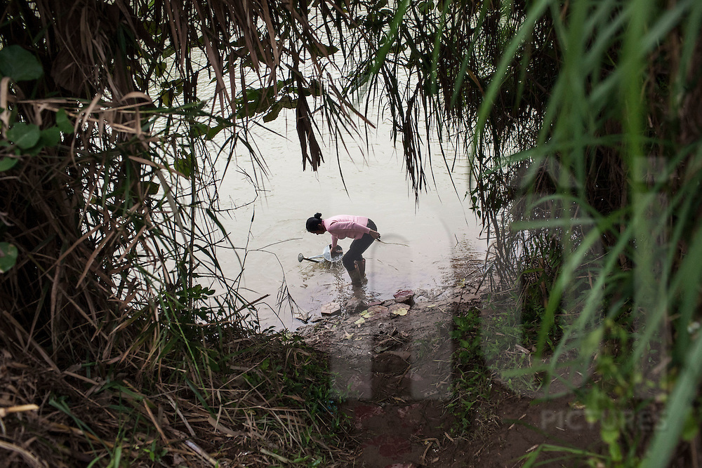 A Vietnamese woman fills her watering can in the Red River, Lao Cai Province, Vietnam, Southeast Asia