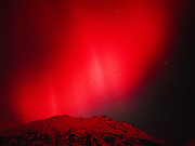 View to the north of brillliant red aurora illuminating the Talkeetna Mountains, geomagnetic storm on the evening of November 5, 2001, Little Susitna River valley, Alaska.
