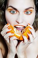 studio portrait of a beautiful woman holding orange mandarine citrus fruit