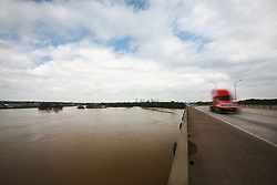 View of flooded Trinity River from I-45 with downtown in background, Dallas, Texas, USA.