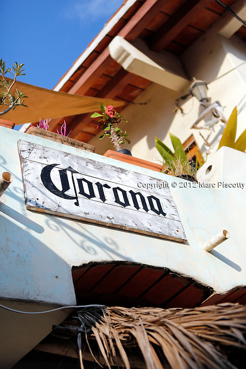 """SHOT 11/10/12 8:34:10 AM - Corona signage above a bar in Sayulita, Mexico. Sayulita is a small fishing village about 25 miles north of downtown Puerto Vallarta in the state of Nayarit, Mexico, with a population of approximately 4,000. Known for its consistent river mouth surf break, roving surfers """"discovered"""" Sayulita in the late 60's with the construction of Mexican Highway 200. In recent years, it has become increasingly popular as a holiday and vacation destination, especially with surfing enthusiasts and American and Canadian tourists. .(Photo by Marc Piscotty / © 2012)"""
