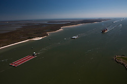 Commercial oil tankers, barges, and shipping vessels underway on the Houston Ship Channel.